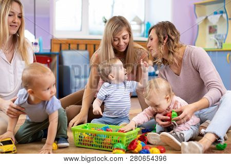 Group Of Moms And Their Babies Playing In Day Care Center