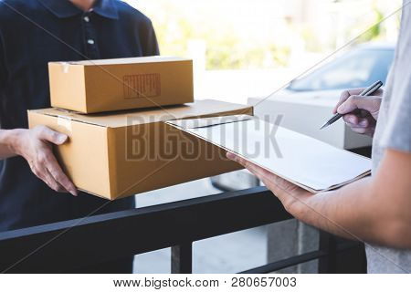 Delivery Mail Man Giving Parcel Box To Recipient, Young Man Signing Receipt Of Delivery Package From