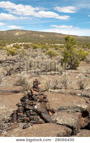 lava flow rock, trail marker and desert vegitation