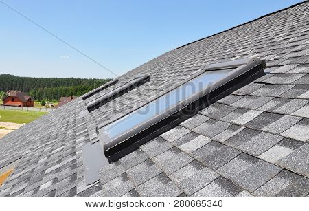 Skylights Windows On Modern House Roof Top.  Attic Skylight Windows On Asphalt Shingles Roof.