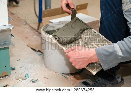 Closeup Professional Builder's Hand Smears Cement Glue On The Ceramic Tile With Trowel To Glue In Ba