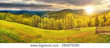 Panorama Of Mountainous Countryside In Springtime At Sunset. Beautiful Highland Landscape. Wooden Fe