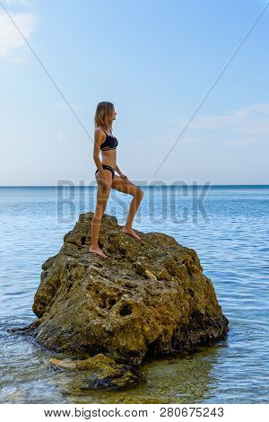 Young Girl Standing On A Big Stone In The Sea