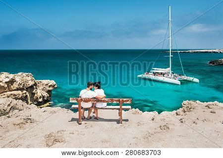 Honeymoon Traveller Couple Hugging On A Wooden Bench And Enjoys Their Tropical Holiday. Wedding Trav