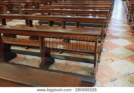 many wooden empty church desks also called pews  in th church without the faithful symptom of a profound serious religious crisis of current Catholicism poster