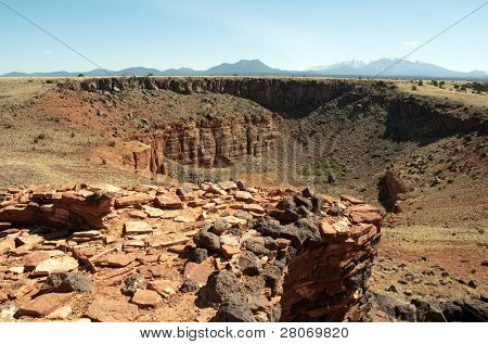 red and volcanic rock wilderness and snow capped mountains