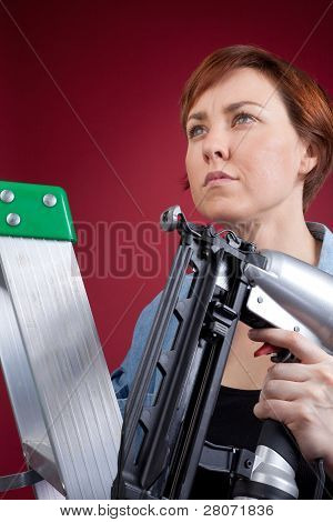 Woman On Ladder Holding Nail Gun