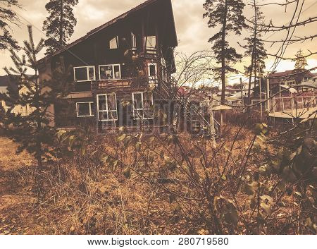 Little Wooden Cottage In The Autumn Forest. Forest With Bare Trees And Dry Fallen Orange Autumn Leav