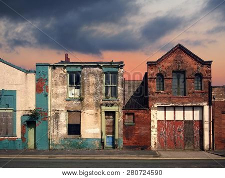 A Deserted Street Of Old Abandoned Ruined Houses With Bright Peeling Paint And Crumbling Brickwork I