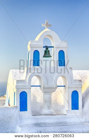 Famous European Destinations. Classic White Roofed Chirch With Blue Inserts And Bell On Oia Village