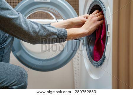 Image of woman folding clothes into washing machine