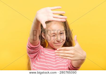 girl pretending to take a picture through her hands creating a virtual photo frame. arts hobby and leisure. poster