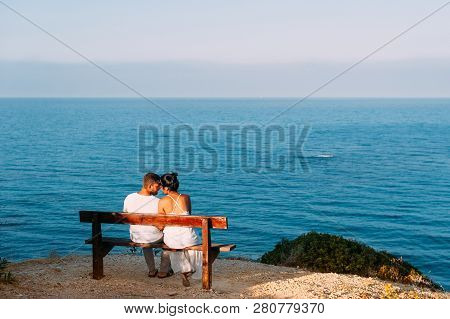 Couple In Love At Sunset. Man And Woman At Dawn. Couple Sitting On A Bench By The Sea. Couple Kissin