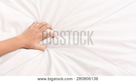 Ecstasy. Female hand grasping white crumpled bed sheet, feeling sexual pleasure or orgasm, panorama, copy space poster