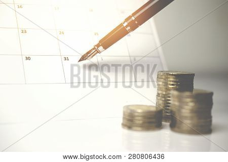A Pile Of Coins And A Blue Tack On The Calendar.