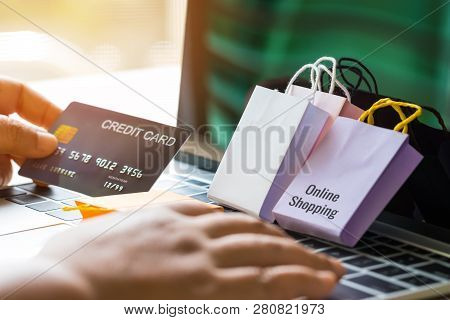 Left Hand Holding Mock Up Of Credit Card And Right Hand Is Using Laptop Keyboard And Paper Shopping