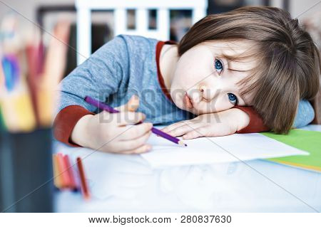Portrait Kid Girl Holding Colour Pencil Sitting Alone And Looking Out With Bored Face