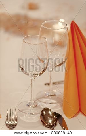 Wineglasses And Folded Table Napkin Tishue On Restaurants Table Covered With White Tablecloth. Cutle