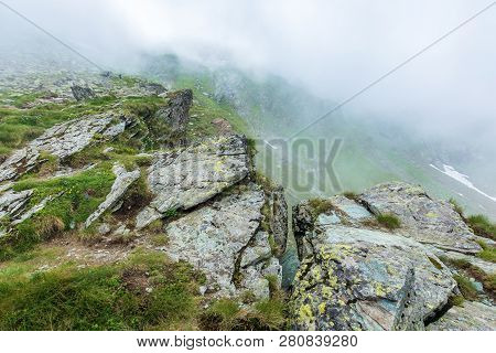 On The Edge Of Rocky Cliff Of Fagaras Ridge. Mysterious Scenery Of Romanian Highlands In Thick Fog.