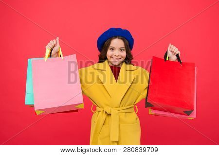 Get Major Wardrobe Refresh With Spring Sales At Stores. Girl Cute Kid Hold Shopping Bags Red Backgro