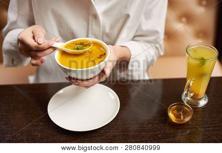 Crop Of Young Female Eating Tasty Orange Cream Soup. Woman In Blouse Enjoying Tasty First Dish In Lu