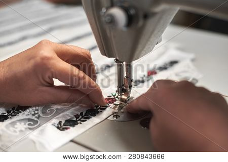 Woman Seamstress Hands Connecting White Fabric Details With Floral Colorful Embroidery With Stripes