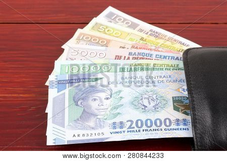 Guinean Money In The Black Wallet On A Wooden Background