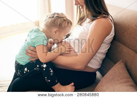 Side View Of Happy Pregnant Mother Sitting On Sofa And Cute Daughter Kissing And Embracing Big Belly