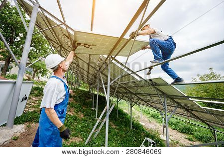 Installing of solar photo voltaic panel system. Three technicians lifting heavy solar module on high platform. Investment in alternative energy, money saving and professional construction concept. poster
