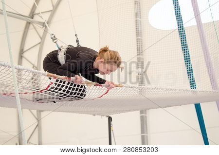 An Adult Female Lands On A Net, Preparing To Dismount At A On A Flying Trapeze School At An Indoor G