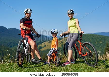 Young Modern Family Tourists Bikers, Mom, Dad And Child Resting On Bikes Looking In Camera On Grassy