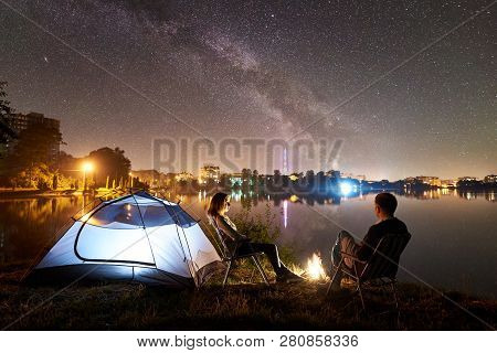 Night Camping On Lake Shore. Man And Woman Having A Rest Near Tent, Couple Sitting On Chairs Near Bo