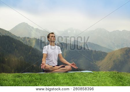 Young Man In Meditation. Outdoor Yoga In Mountains