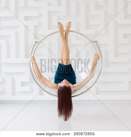 Young Brunette Woman Wearing Elegant Blue Dress Levitate On Round Glass Chair
