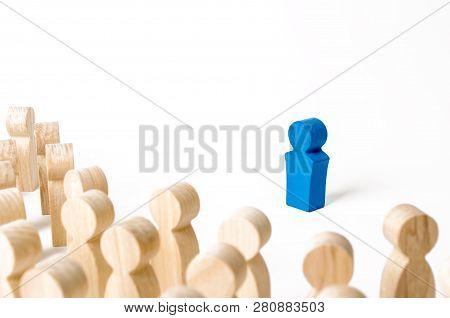 Blue Human Figurine In The Spotlight Of A Crowd Of People. Leader, Leadership, Head Of Organization