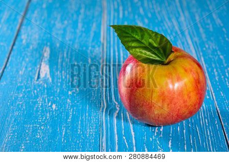 Red Apple On Blue Wooden Background Closeup