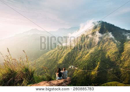 The Couple Greets The Sunrise In The Mountains. Man And Woman In The Mountains. Wedding Travel. The