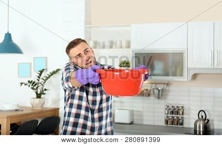 Emotional Young Man Calling Plumber While Collecting Water Leakage From Ceiling In Kitchen