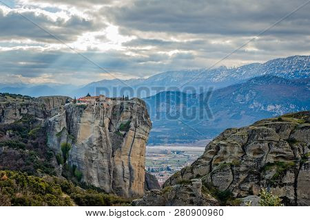 Agios Stephanos Or Saint Stephen Monastery Situated On The Huge Rock With Sunset Rays And Mountains