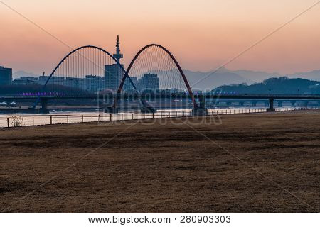 Daejeon,south Korea; January 17, 2019;  Field Of Brown Grass In Front Of Bridge And Double Arches At