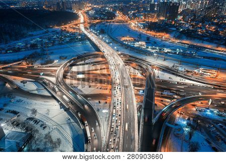 Aerial View Of Road In The Modern City At Night In Winter. Top View Of Traffic In Highway, Buildings