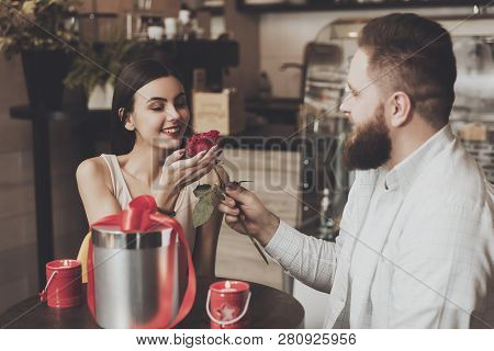 Bearded Man Gives A Rose To Beautiful Smiling Girl. A Young Man With A Beautiful Young Girl Sitting