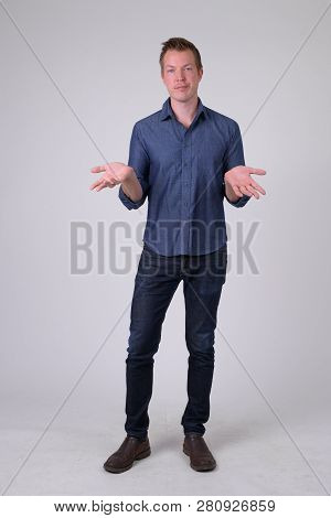 Full Body Shot Of Confused Young Businessman Shrugging Shoulders