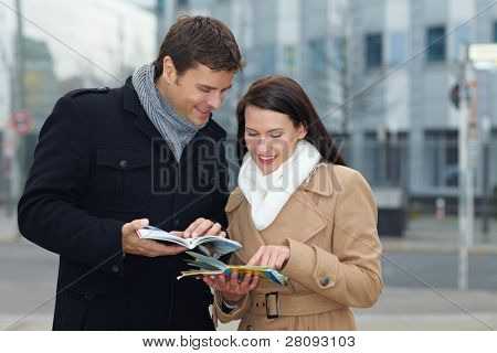 Happy tourists on holiday with tour guide and city map