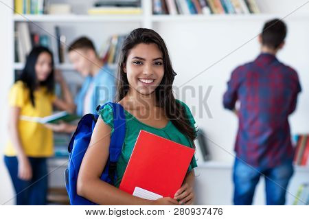 Laughing Latin American Female Student With Group Of Students At Library Of University