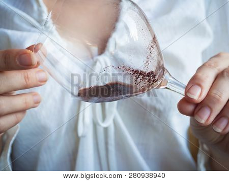 The Glass With The Sediment In The Wine In His Hands.