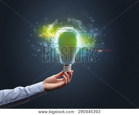 Hand holding light bulb on dark background. New business idea concept