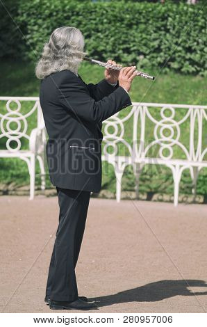 Tsarskoye Selo, Saint Petersburg, Russia - May 20, 2016: Gray-haired Street Flutist In A Black Suit