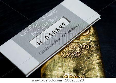 The Certificate Of Assay For Gold Bars Lies On A Cast Gold Ingot. Gehaltszertifikat Für Goldbarren I