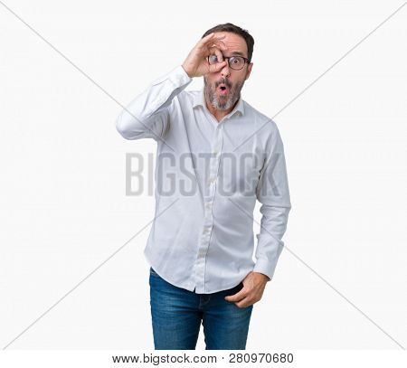 Handsome middle age elegant senior business man wearing glasses over isolated background doing ok gesture shocked with surprised face, eye looking through fingers. Unbelieving expression.